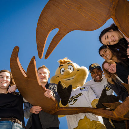Student leaders all hanging around the Scorpion Statue with NSC mascot