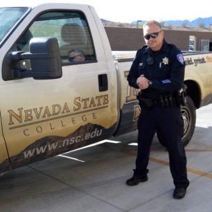 Campus police officer standing next to NSC truck