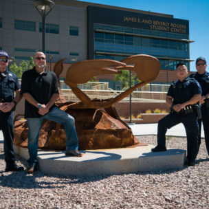 Three police officers standing in front of Scoprion Statue with former facilities director