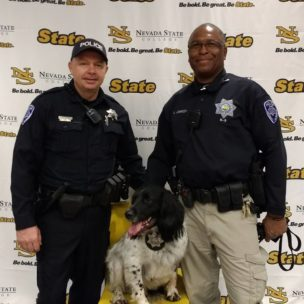 Two male police officers standing happily with police dog