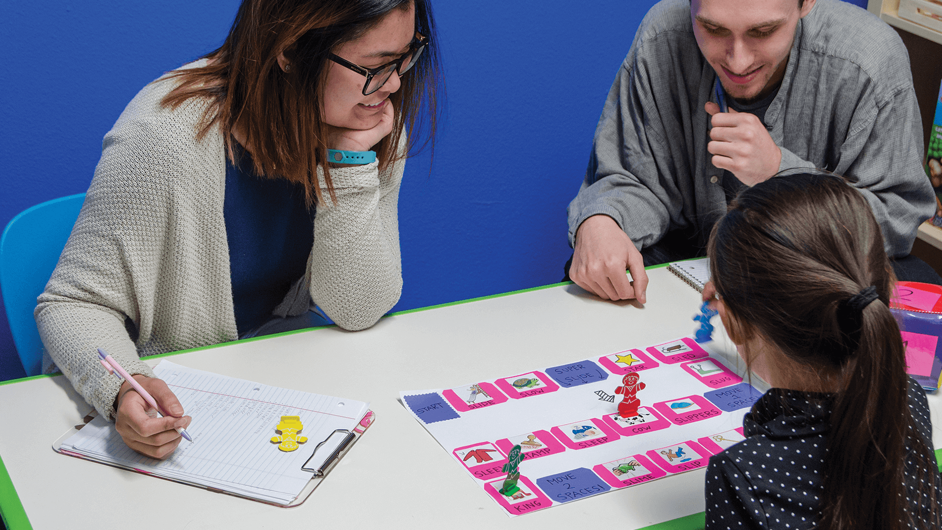 Adult male playing a board game with female child, as adult female students watches and takes notes