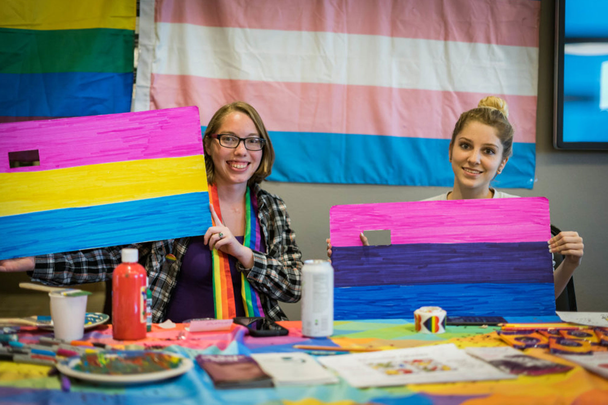 Picture of two female students holding up painted flags for different sexual and gender identities