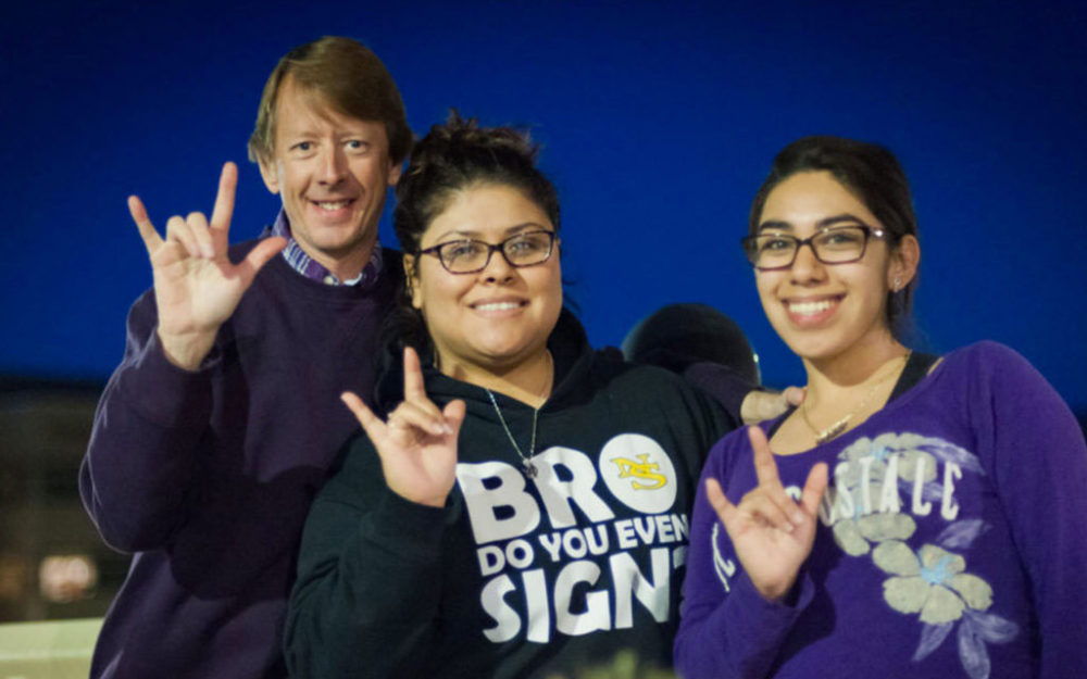 Picture of a NSC Professor and two students showing American Sign Language sign for