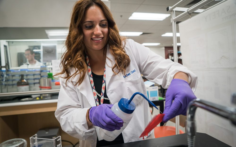 Student working in a lab with a white coat on using distilled water