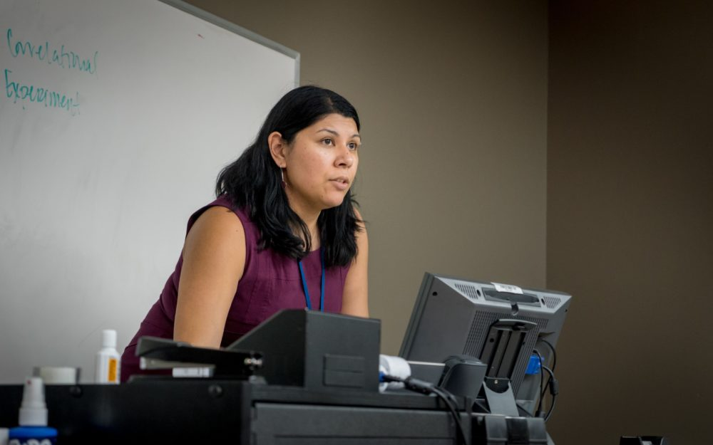Picture of Psychology Professor, Dr. Laura Naumann at the front of the classroom behind a computer