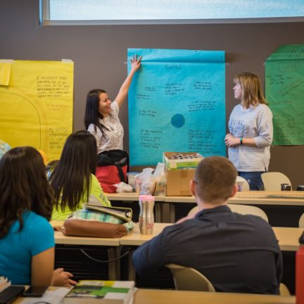 Two students presenting in front of class with poster on wall