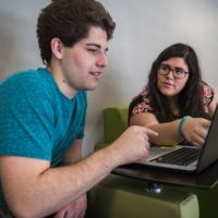 Two students working on laptop together